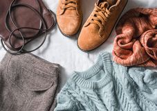Women`s clothing set - skirt, suede boots, sweater, scarf, leather  bag on a light background, top view. Winter, fall female clot. Hing. Flat lay Royalty Free Stock Images