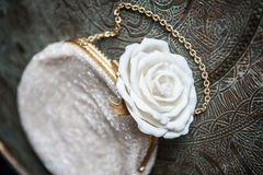 Women's clutch  with white rose on brass tray with an ornament Stock Photos