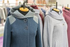 Women's coat in the store. Spring women's coats hanging on a rack in a women's clothing store stock photo
