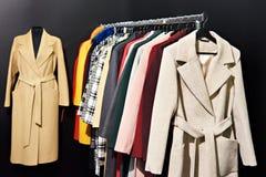 Women`s coats on hanger in store on black. Women`s coats on a hanger in the store on a black background stock images