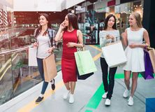 Women`s company is in mall. They are split on two groups. Girl in red dress is talking on the phone while asian girl is. Showing phone to her blonde friend stock images