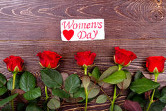 Women`s Day card above roses. Heart and red wet flowers. Surprise your wife. Simple way of giving present royalty free stock images