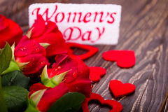 Women`s Day card and flowers. Hearts and wet roses. Express by actions, not words. Gift for charming lady Royalty Free Stock Images