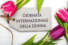 Women`s day card with Italian words `Giornata internazionale della donna`. Tulip flower and small heart on white wooden background Royalty Free Stock Photography