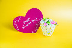 Women`s day concept. Basket with flowers and paper heart with Happy Women`s Day on golden background Stock Image