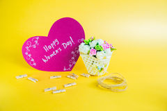 Women`s day concept. Basket with flowers and paper heart with Happy Women`s Day on golden background Stock Images