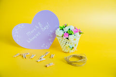 Women`s day concept. Basket with flowers and paper heart with Happy Women`s Day on golden background Stock Photography