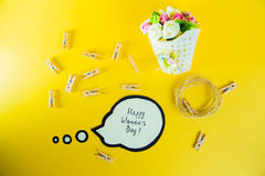 Women`s day concept. Inscription on paper Happy Women`s Day and a basket with flowers, rope and clothespins on golden Royalty Free Stock Photos