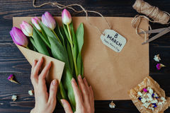 Women`s day. Florist preparing bouquet of fresh beautiful tulips on the wooden table. Stock Photography