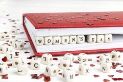 Women`s Day greeting message written in wooden blocks in red not. Ebook on white table. Background for International Womens Day, March 8 royalty free stock photo