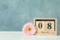 Women`s day March 8 with wooden block calendar. Happy mothers day. Spring flower on white table. Space for text