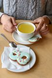 A Women`s day photo of woman`s hands, a tea pot, a cup and a cookie shaped like a figure `8`. A festive Women`s day photo of woman`s hands, a tea pot, a cup and royalty free stock photos