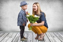 Small son gives his beloved mother a bouquet of beautiful tulips. Spring, concept of family vacation. Women`s day. royalty free stock photo