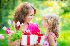 Women's day. Woman and child with bouquet of flowers against green blurred background. Spring family holiday concept. Women's day