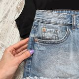 Women`s denim shorts on a wooden background stock images