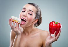 Women's diet. Donut or bell peppers ? Royalty Free Stock Image