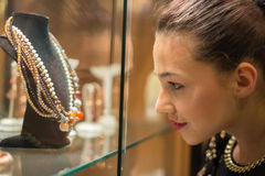 Women's Dream. Young woman looking on the jewelry shop window royalty free stock photos