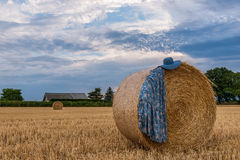 Women's dress and hat on a haystack in a field Royalty Free Stock Photo