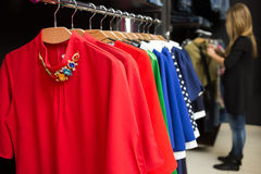Women's dresses on hangers in a retail shop. Colorful women's dresses on hangers in a retail shop royalty free stock image