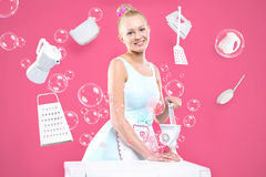 Women's duties - cooking , washing, ironing. Young housewife overwhelmed by tasks associated with running a home. Joyful woman does housework. Colourful Stock Image