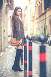 Women`s fashion. Beautiful young woman standing in the city. Royalty Free Stock Photo