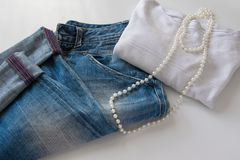 Women`s fashionable casual outfit - blue jeans, white sweater and white pearl necklace. Space for text Royalty Free Stock Image