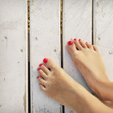 Women's feet on the boards of the pier Royalty Free Stock Image