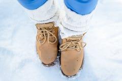 Women`s feet in fashion trekking boots in the snow, winter touri Royalty Free Stock Photos