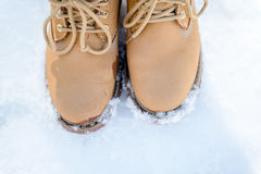 Women`s feet in fashion trekking boots in the snow, winter touri Royalty Free Stock Images