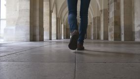 Women's feet go through the hall of columns stock video