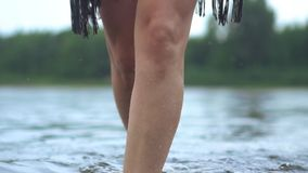 Women`s feet in water. Women`s feet go into the river in cloudy weather in the rain stock footage