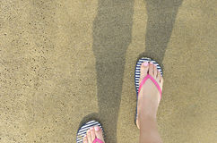 Women`s feet go on the wet sand beach. Female feet in the shales flow along wet sand of the beach Stock Images