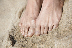 Women's feet in golden sand Stock Images