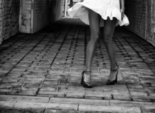 Women`s feet in heels in a dark alley of the city.  royalty free stock photos