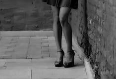 Women`s feet in heels in a dark alley of the city.  stock image