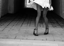 Women`s beautiful slender legs in heels. Women`s feet in heels in a dark alley of the city, Women`s feet in heels in a dark alley of the city royalty free stock image