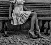 Women`s beautiful slender legs in heels. Women`s feet in heels in a dark alley of the city, Women`s feet in heels in a dark alley of the city royalty free stock photography