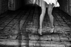 Silhouette of a woman in a dark alley of the city. Women`s feet in heels in a dark alley of the city, Women`s feet in heels in a dark alley of the city stock photos
