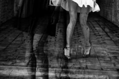 Silhouette of a woman in a dark alley of the city. Women`s feet in heels in a dark alley of the city, Women`s feet in heels in a dark alley of the city stock image