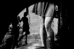 Silhouette of a woman in a dark alley of the city. Women`s feet in heels in a dark alley of the city, Women`s feet in heels in a dark alley of the city stock photography