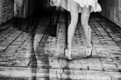 Silhouette of a woman in a dark alley of the city. Women`s feet in heels in a dark alley of the city, Women`s feet in heels in a dark alley of the city royalty free stock images