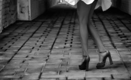 Women`s feet in heels in a dark alley of the city.  royalty free stock photo