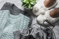 Free Women`s Feet In Cozy Soft Slippers, Bunch Of Winter Autumn Women`s Sweaters, Basket Of Clothes, Succulents Flower On A Gray Royalty Free Stock Image - 162171276