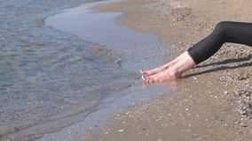 Women`s feet in leggins against the sea in sand beach. royalty free stock images