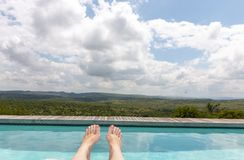 Women`s Feet Over The Pool royalty free stock photo