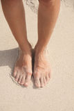 Women's feet in the sand Stock Photo