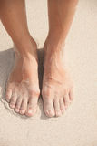 Women's feet in the sand Stock Images