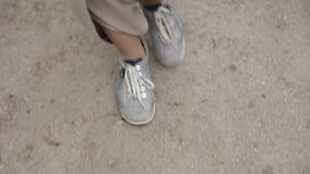 Women`s feet in sneakers are on the asphalt.  stock video