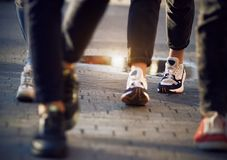 Women`s feet in sports shoes among the crowd of passers royalty free stock image