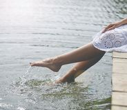 Women`s feet in the water. Plunges feeling freshness Stock Image